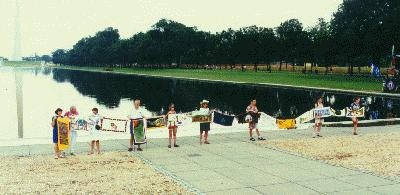 Washington, DC – several people holding multiple ribbon panels by the Capital's reflecting pool.